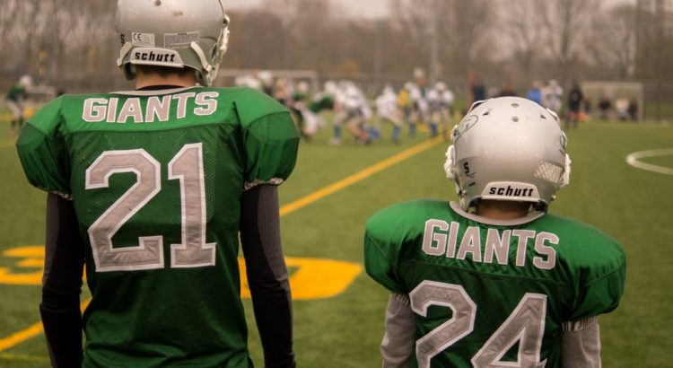 One large and one small youth football players standing on the sidelines.