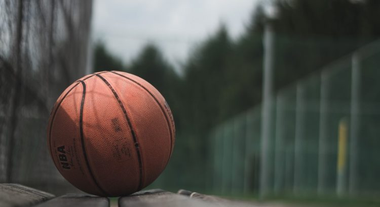 A basketball sits on an outdoor bench.