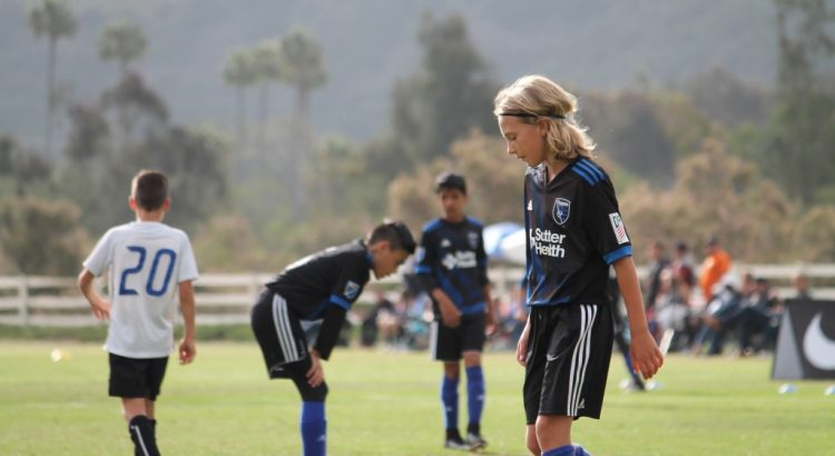 Youth soccer team hangs heads in defeat.